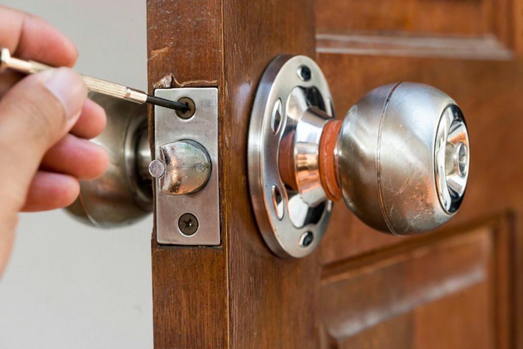 closeup of locksmith on old wood door , repair